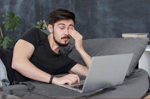 man falling asleep using laptop.adrenal burnout maybe
